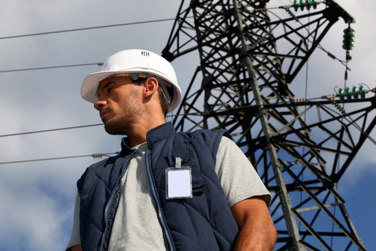 photodune-3104892-worker-standing-in-front-of-an-electricity-pylon-xs